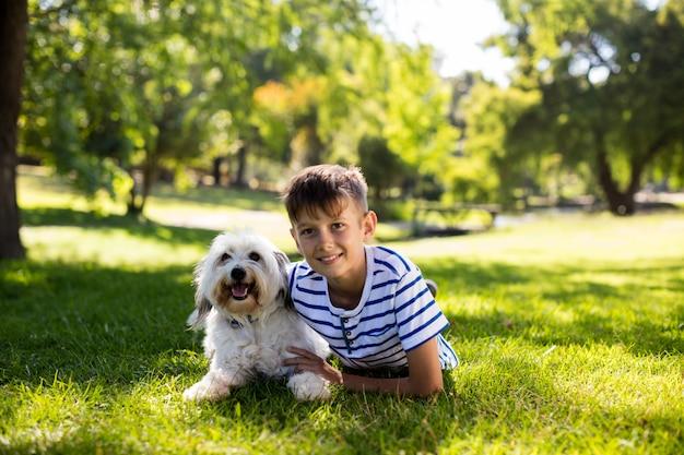 Portret chłopca z psem w parku