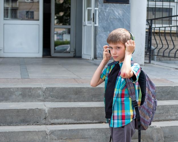 Portret chłopca z tornister w słuchawkach przed szkołą. powrót do koncepcji szkoły