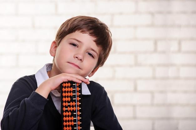 Portret chłopca ze szkoły podstawowej z liczydła.