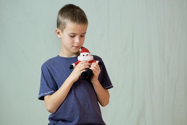 Portret chłopiec dziecko bawi się małą zabawką świętego mikołaja.