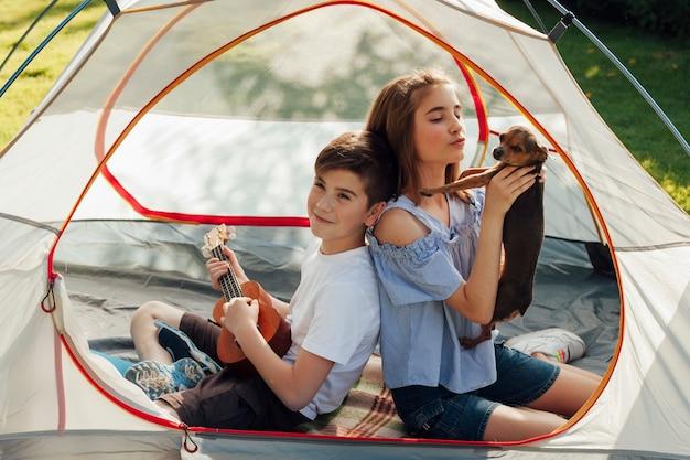 Portret chłopiec i dziewczyny obsiadanie w namiocie z trzymać psa i ukulele