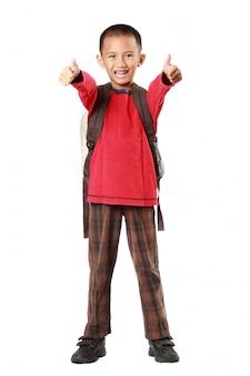 Portret chłopiec ono uśmiecha się pokazywać kciuka up znaka z plecakiem przeciw bielowi