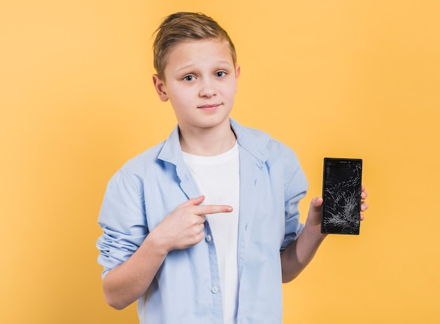 Portret chłopiec pokazuje łamanego smartphone z rozbijającym ekranem przeciw żółtemu tłu