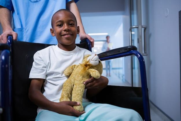 Portret chłopiec siedzi na wózku inwalidzkim i trzyma misia w korytarzu