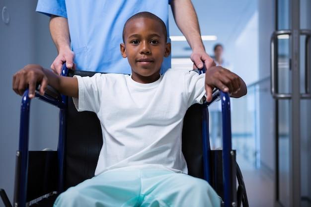 Portret chłopiec siedzi na wózku inwalidzkim w korytarzu