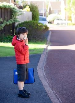 Portret chłopiec w szkole jedzący czerwone jabłko, aktywne dziecko w szkole stojące na zewnątrz, czekające rano na autobus szkolny, koncepcja powrotu do szkoły, pięć dziennie jedzenia dla dzieci