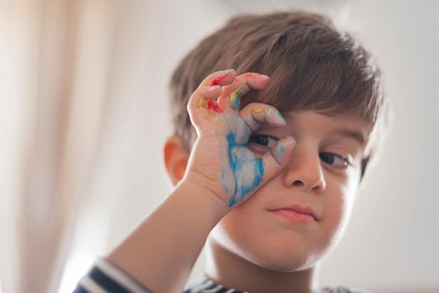 Portret chłopiec z farbą na ręce