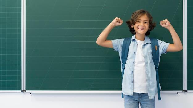 Portret chłopiec z plecakiem przy szkołą