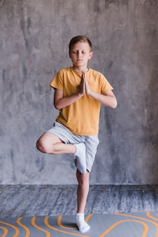 Portret chłopiec z zamkniętymi oczami stoi w joga pozie na jeden nodze