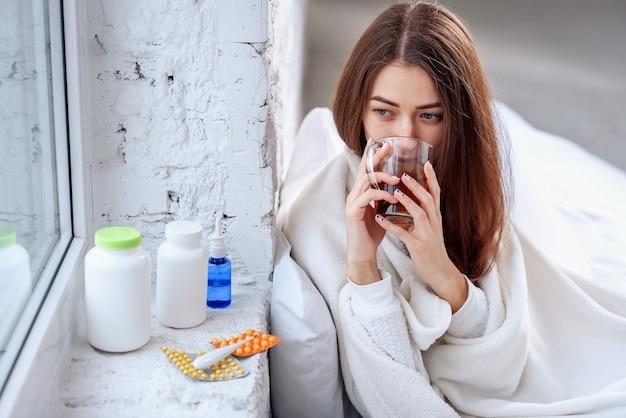 Portret chora niezdrowa dziewczyna pije nagrzanie napój w pomieszczeniu