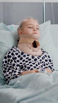 Portret chorego dziecka leżącego w łóżku, patrzącego na kamerę, mając na szyi kołnierz szyjny