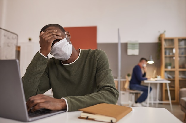Portret chorego i zmęczonego african-american człowieka noszącego maskę i za pomocą laptopa podczas pracy przy biurku w biurze, kopia przestrzeń