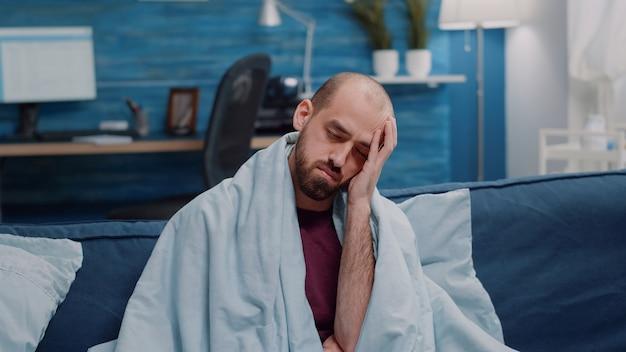 Portret chorego mężczyzny z bólem głowy, patrząc na kamerę