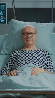 Portret chorego pacjenta leżącego w łóżku na oddziale szpitalnym