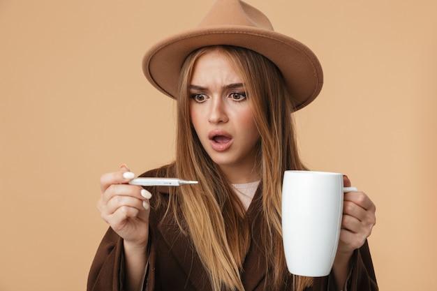 Portret chorej kaukaskiej dziewczyny w kapeluszu trzymającym termometr i filiżankę gorącej herbaty na beżowym tle