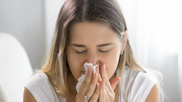 Portret chorej młodej kobiety, która kicha i dmucha nos w papierową chusteczkę