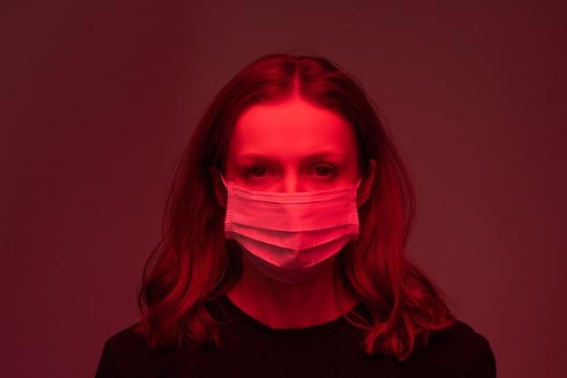 Portret chorej młodej kobiety w jednorazowej masce stojącej w ciemnoczerwonym pokoju