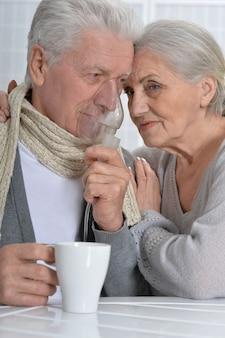 Portret chorej pary seniorów z inhalatorem
