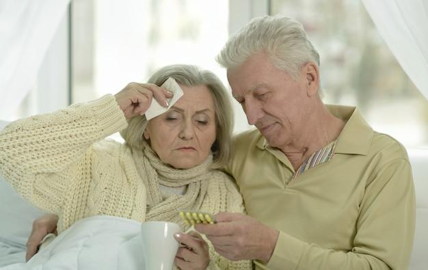 Portret chorej starszej kobiety z mężem w łóżku