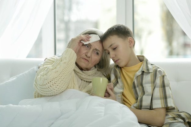 Portret chorej starszej kobiety z wnukiem w łóżku