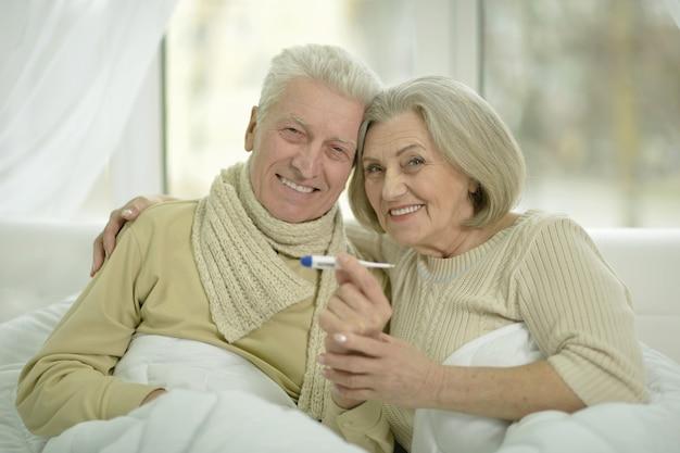 Portret chorej starszej pary w łóżku z termometrem