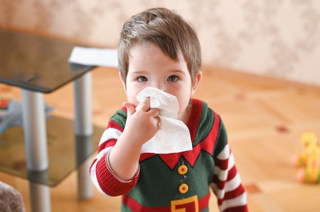 Portret chory chłopiec czyści nos serwetką. koncepcja sezonu grypowego