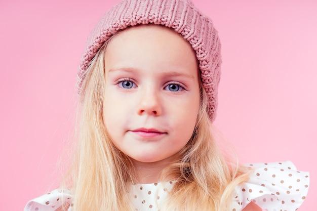 Portret ciała urocza dziewczynka blond dziewczyna niebieskie oczy modelu w beżowy dzianinowy różowy kapelusz w białej sukni księżniczki w groszku, jesienny sezon wiosenny w studio strzał na różowym tle.
