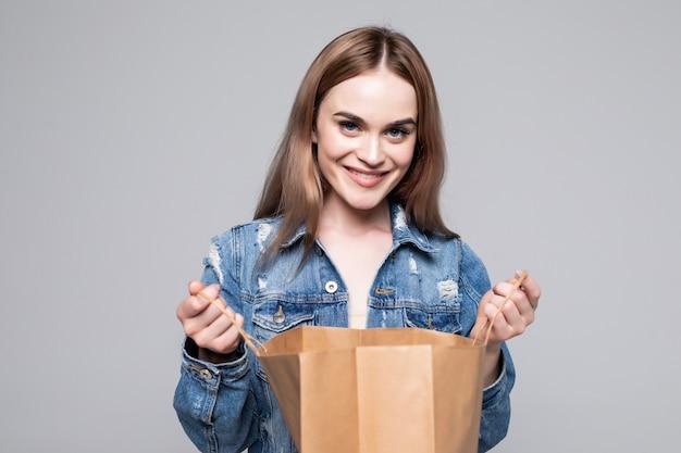 Portret ciekawa młoda kobieta patrzeje inside torba na zakupy nad szarości ścianą