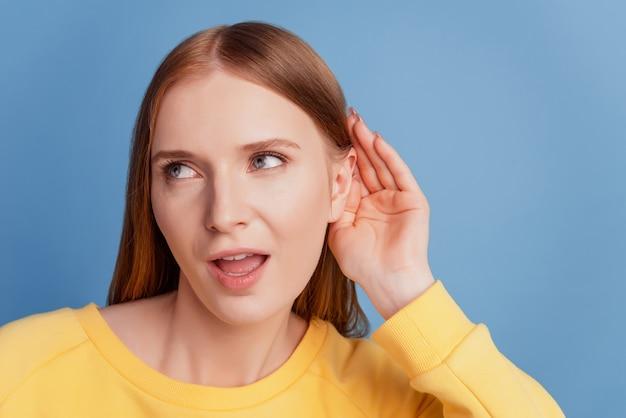 Portret ciekawa, podstępna dama podsłuchująca ucho palmowe wygląda na pustą przestrzeń na niebieskim tle
