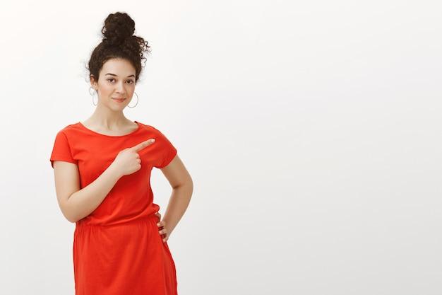 Portret ciekawy, kreatywny atrakcyjna kobieta z kręconymi włosami w fryzurę kok, uśmiechając się i wskazując w prawo palcem wskazującym