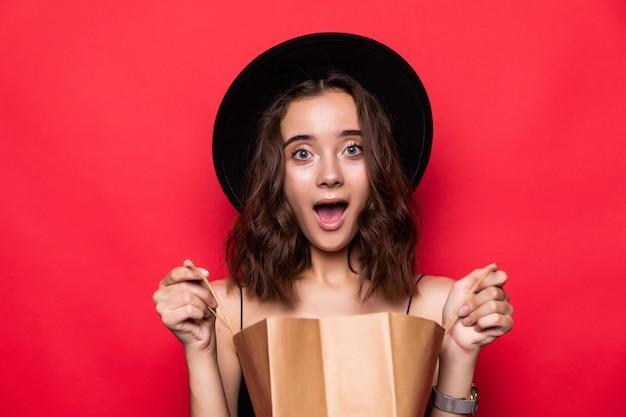 Portret ciekawy młoda kobieta w kapeluszu lato patrząc wewnątrz torby na zakupy na białym tle nad czerwoną ścianą