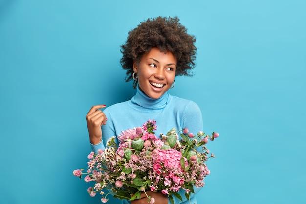 Portret ciemnoskóra kobieta z kręconymi włosami wygląda z radością z dala, trzyma piękne bouqet pozach na niebieskim tle