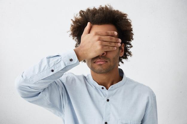 Portret ciemnoskórego mężczyzny rasy mieszanej z krzaczastą fryzurą w białej koszulce zakrywającej twarz