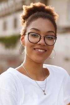Portret ciemnoskórej dziewczyny w okularach w lecie na ulicy
