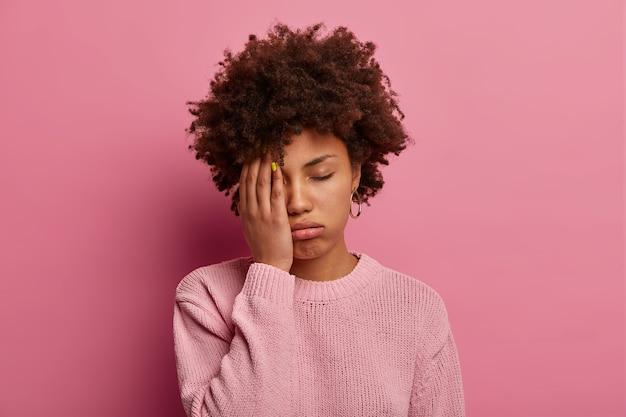 Portret ciemnoskórej kobiety zasłania połowę twarzy, wzdycha ze zmęczenia