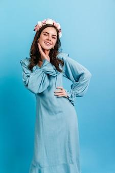 Portret ciemnowłosej damy w eleganckiej, delikatnie niebieskiej sukience. dziewczyna z koroną kwiatów jest urocza uśmiechnięta.