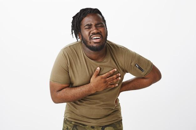 Portret cierpiącego faceta w brązowej koszulce pozuje na białej ścianie
