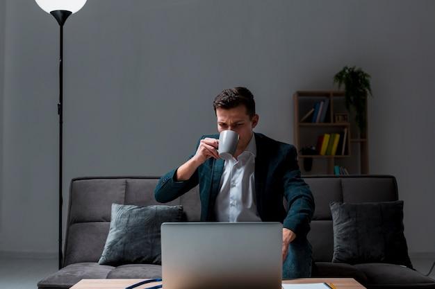 Portret cieszy się kawę dorosła samiec podczas gdy pracujący przy nocą