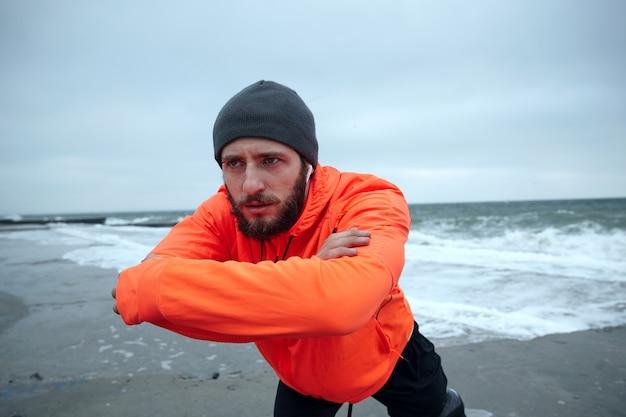 Portret ciężkiego sportowego młodego bruneta z brodą słuchającego muzyki w słuchawkach podczas ćwiczeń i biegania nad morzem, prowadząc zdrowy, aktywny tryb życia
