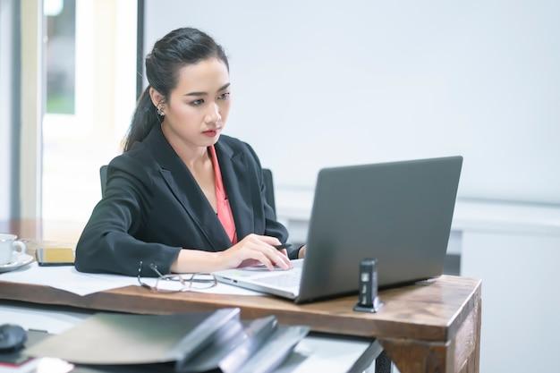 Portret comfident młody przedsiębiorcy bizneswoman pracuje z pastylką lub urządzeniem przenośnym w pracującej staci.