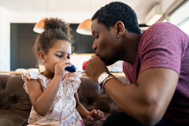 Portret córki i ojca, wspólnej zabawy i gry z balonami w domu. koncepcja monoparental.