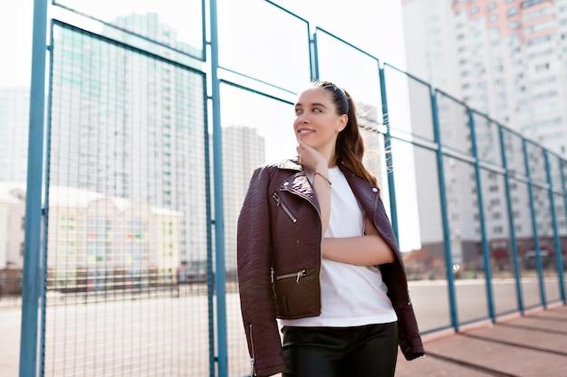 Portret cudownej białej modelki z jasnym makijażem wyrażającej energię na dobry dzień w metropolii