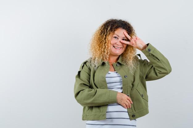 Portret cudownej kobiety pokazującej znak v na oku w zielonej kurtce, koszuli i patrząc radosny widok z przodu