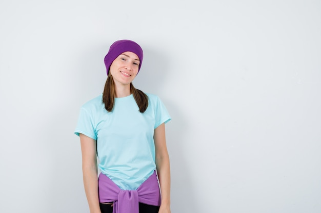 Portret cudownej kobiety pozującej stojąc w bluzce, czapce i patrząc pewnie z przodu