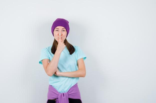 Portret cudownej kobiety trzymającej palec na nosie w bluzce, czapce i patrzącej pozytywnie z przodu
