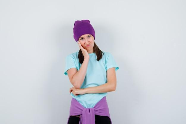 Portret cudownej kobiety trzymającej rękę na policzku w bluzce, czapce i patrzącej na zaniepokojony widok z przodu