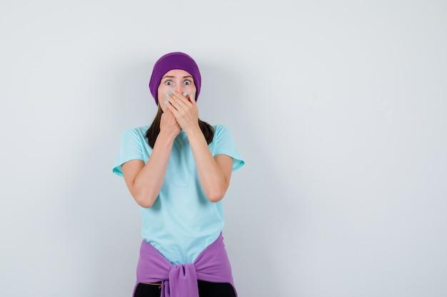 Portret cudownej kobiety zakrywającej usta rękami w bluzce, czapce i patrzącej w szoku z przodu