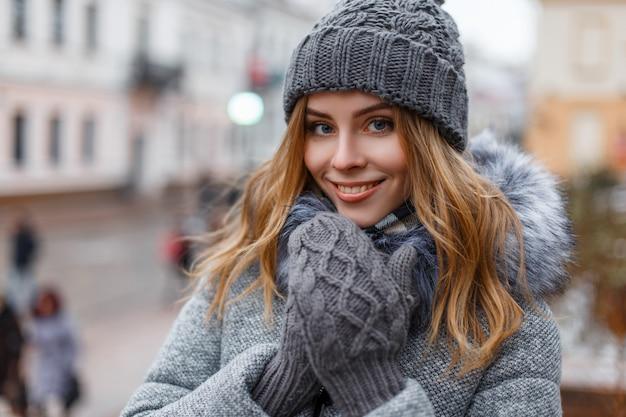 Portret cudownej młodej kobiety o pięknych niebieskich oczach z naturalnym makijażem w słodkim uśmiechu w dzianinowej czapce w dzianinowych rękawiczkach w stylowym płaszczu na ulicach miasta. wesoła dziewczyna.