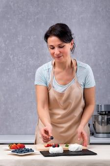 Portret cukiernika dekaruje ciasta lub bezę. rama pionowa.