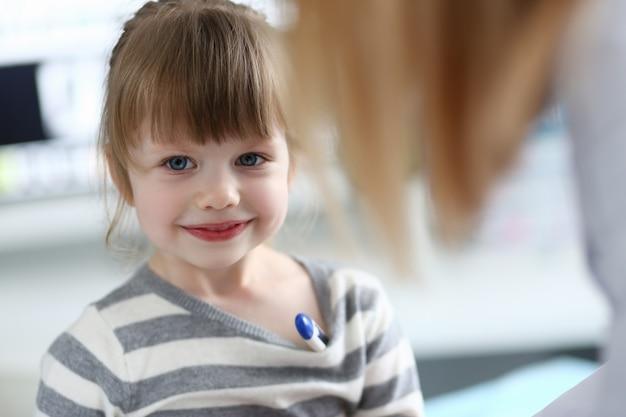 Portret cute dziewczynka siedzi w gabinecie lekarskim z termometrem